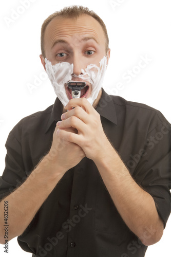 portrait of a male trying to shave against white
