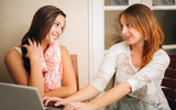 Two young girlfriends talking in front of computer