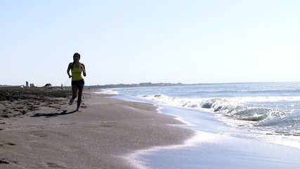 Woman running on the beach jogging