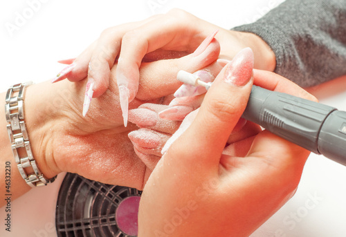 Manicure process in beauty salon showing polishing of nails
