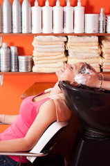 Beautiful young girl enjoying hair washing in hairdressing salon