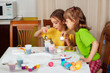 Two little girls (sisters) painting on Easter eggs