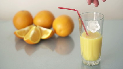 Ice cube falling in glass with orange juice, super slow motion