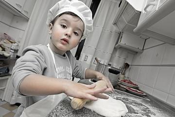 Pequeño cocinero preparando una masa de pan en la cocina