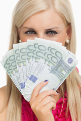 Green eyed woman holding 100 euros banknotes