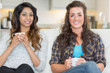 Two women holding cups of coffee