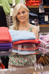 Woman standing at a clothes rack smiling