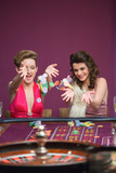 Women throwing chips on roulette table