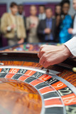 Dealer dropping ball into roulette wheel
