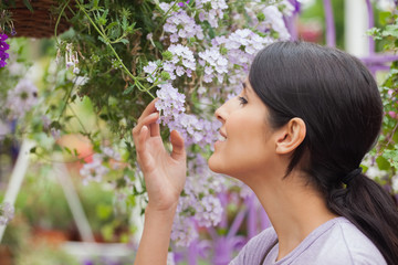 Woman smelling while holding a flower