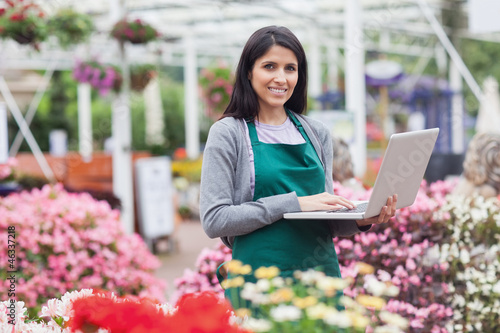 Woman using laptop in the garden center