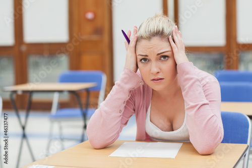Woman looking worried over exam paper