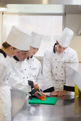 Culinary students learning how to chop vegetables