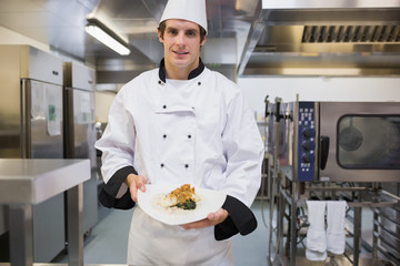 Cheerful chef presenting his plate