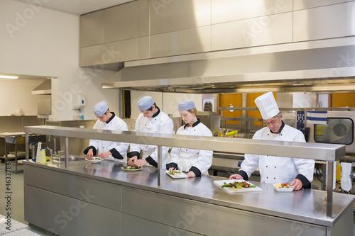 Four Chef's preparing plates
