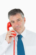 Businessman using red phone