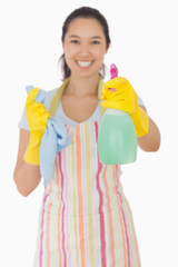 Happy woman holding out spray bottle