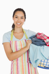 Smiling woman holding laundry basket