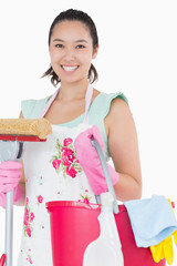 Happy woman holding different cleaning tools