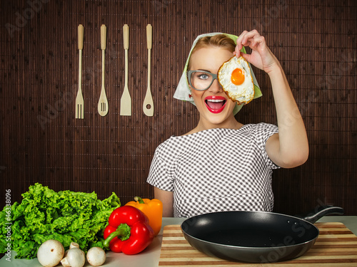 Happy funny woman cook holding pan with fried egg - close up