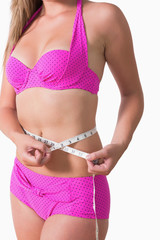 Woman wearing bikini while measuring waist