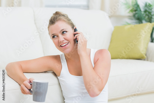 Woman phoning while drinking coffee