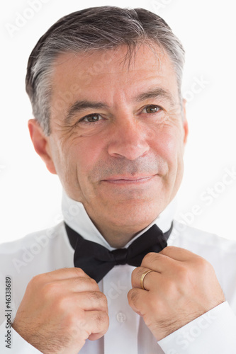 Happy man adjusting his bow tie