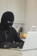 Robber hacking a laptop in the kitchen