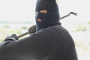 Burglar with crowbar in his hand