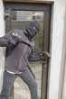 Burglar breaking into home using crow bar