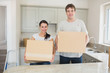 Young man and woman holding moving boxes
