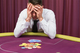 Man holding head in hands at poker table