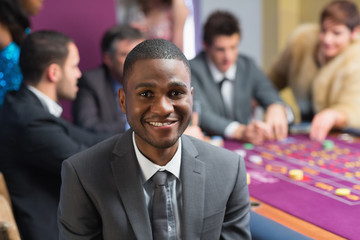 Smiling man sitting at roulette table