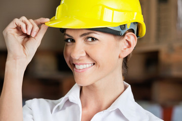 Female Supervisor Touching Hardhat At Warehouse