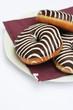 ciambelle glassate al cioccolato su piatto_sfondo bianco