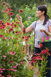 Woman holding a basket while looking at flowers