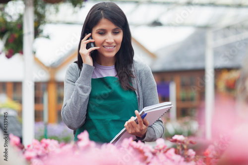 Garden center worker phoning while taking notes