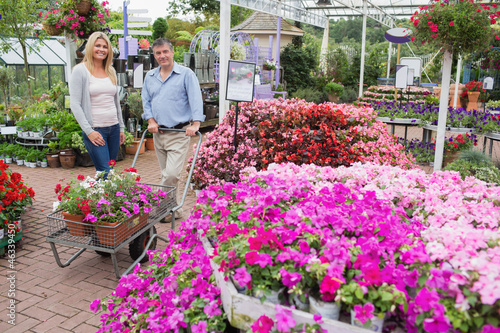 Couple pushing trolley full of flowers