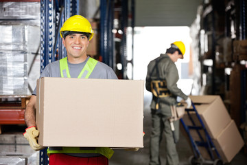 Mid Adult Foreman With Cardboard Box At Warehouse