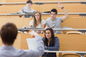 Students sitting at the lecture hall with man razing hand to ask