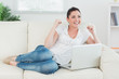 Woman lying on the couch and using a laptop