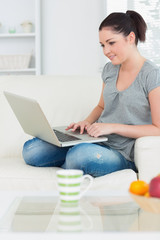 Smiling woman using a laptop on the couch
