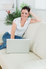 Woman sitting on the couch and smiling while using a laptop