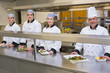 Four smiling Chef's with their dishes
