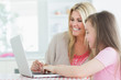 Woman and daughter sitting at the laptop