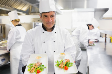 Chef holding out two salmon dishes