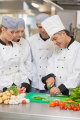 Chef teaching cutting vegetables to three trainees