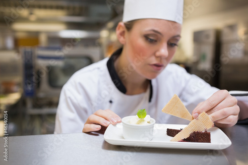 Chef garnishing a slice of cake