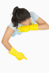 Woman in rubber gloves pointing on white surface