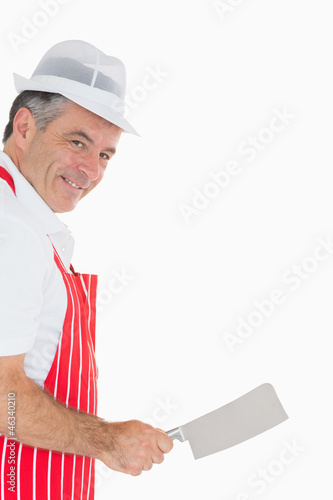 Butcher wielding meat cleaver and smiling